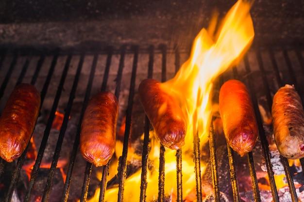 Salchichas a la parrilla sobre los carbones ardientes en una barbacoa portátil