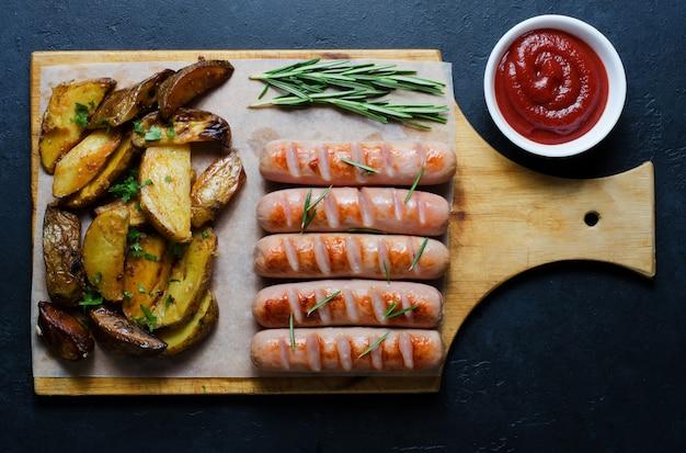Salchichas a la parrilla sobre una tabla de cortar de madera. patatas fritas, romero, salsa de tomate. dieta no saludable. fondo oscuro