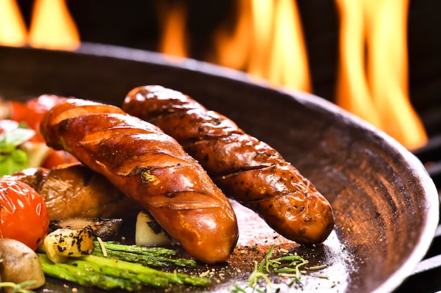 Salchichas a la parrilla y varias verduras en sartén de hierro