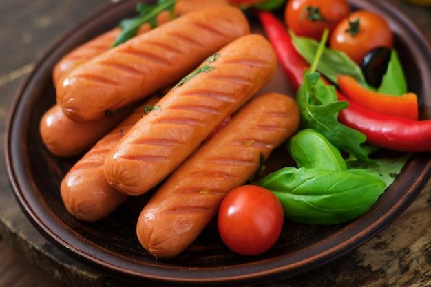 Salchichas a la parrilla y verduras sobre una mesa de madera en estilo rústico.