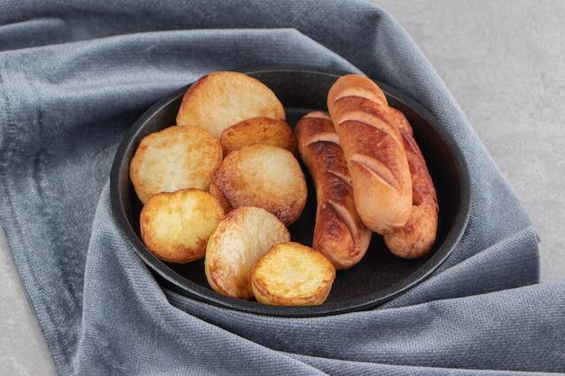 Salchichas y patatas fritas en placa negra.