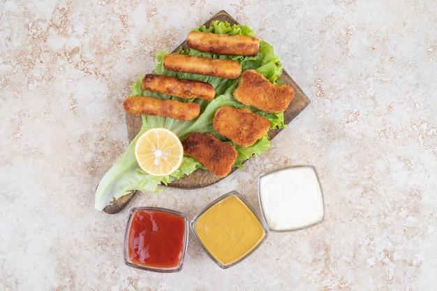 Salchichas a la plancha con nuggets de pollo sobre un trozo de lechuga sobre una tabla de madera con salsas a un lado.