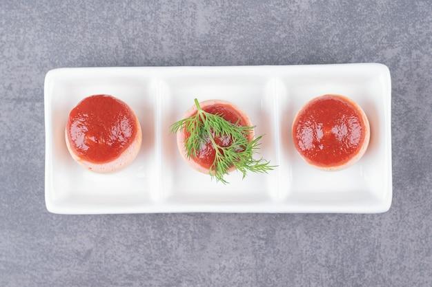 Salchichas en rodajas con salsa de tomate en un plato blanco.
