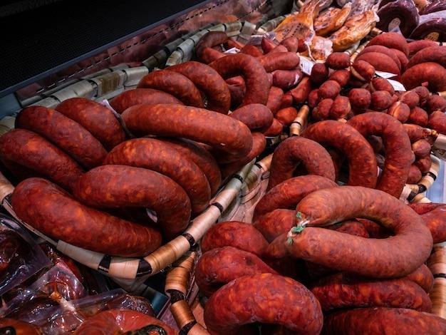 Salchichas rojas tradicionales españolas en carnicería. carne ahumada seca en el supermercado. supermercado comercial de cerdo ibérico. vender productos crudos en el mercado