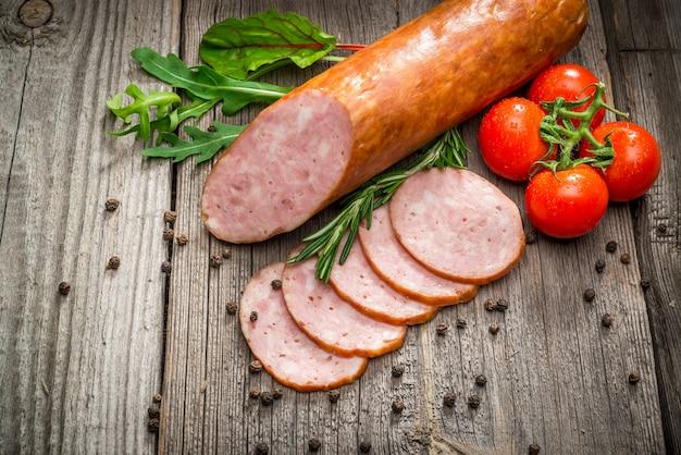 Salchichas de salami en rodajas con pimienta, ajo y romero en tabla de cortar en mesa de madera. vista superior