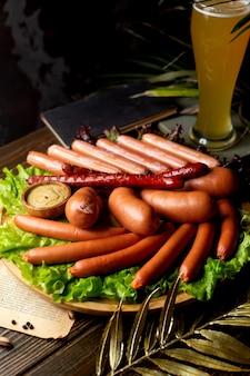 Salchichas servidas con mostaza y cerveza
