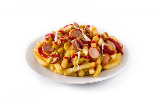 Salchipapa típica de américa latina. salchichas con papas fritas, salsa de tomate, mostaza y mayonesa, en blanco