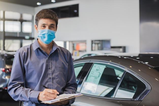 Saleman asiático usar mascarilla quirúrgica trabajando en inspector revisando la escritura en el portapapeles en el garaje del concesionario
