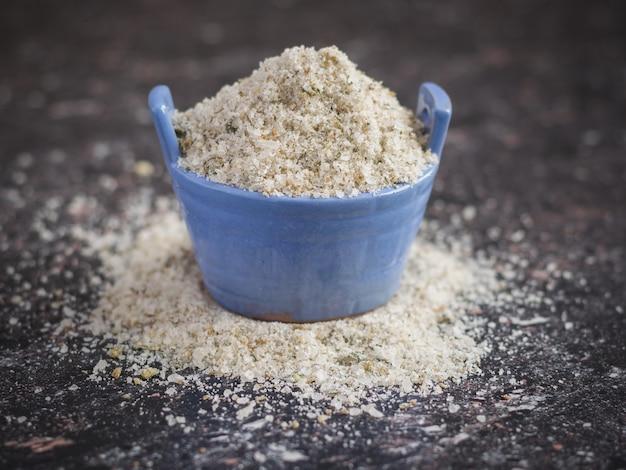 Salero azul lleno de sal, con hierbas sobre la mesa de piedra.