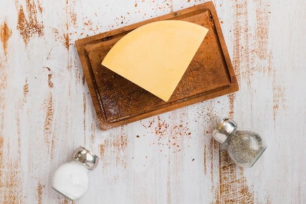 Salero y pimentero negro botellas con queso en la tabla de cortar