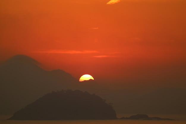 Salida del sol desde la capa de nubes sobre la vista del océano atlántico desde la playa de copacabana en río de janeiro