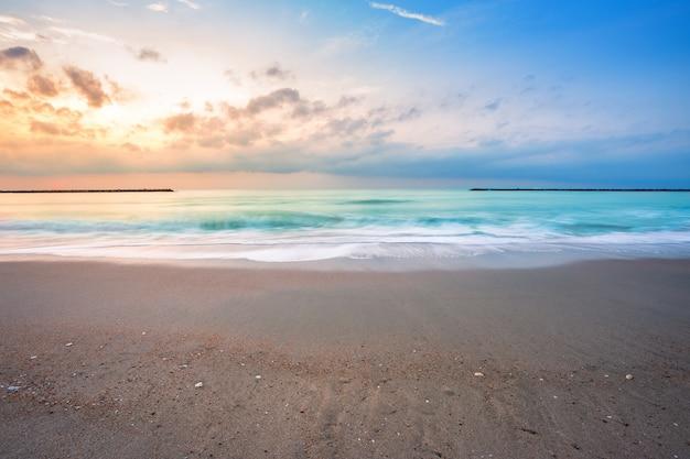 Salida del sol hermosa de la madrugada sobre el mar el horizonte en la playa de chao samran del sombrero en phetchaburi tailandia.