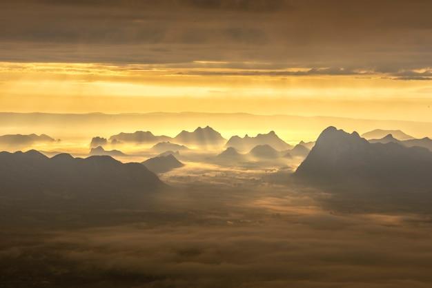 Salida del sol de la mañana con la niebla en las montañas, fondo de la salida del sol.