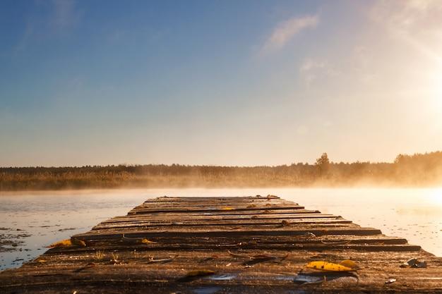 Salida del sol o puesta de sol sobre el río con un muelle de madera.