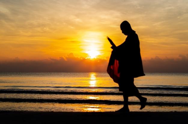 Salida del sol con la reflexión sobre el mar y la playa que han empañado la foto de la silueta del monje budista.