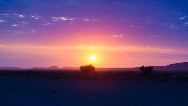 Salida del sol sobre el desierto de namib, en el maravilloso parque nacional namib naukluft, destino de viaje en namibia, áfrica.