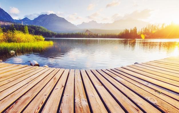 La salida del sol sobre un lago en el parque altos tatras. shtrbske pleso, eslovaquia