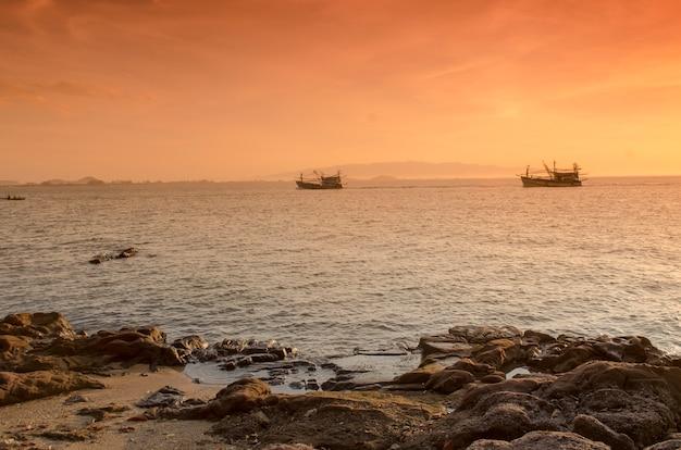Salida del sol sobre el mar y el barco de pesca en el campo, hua hin-tailandia