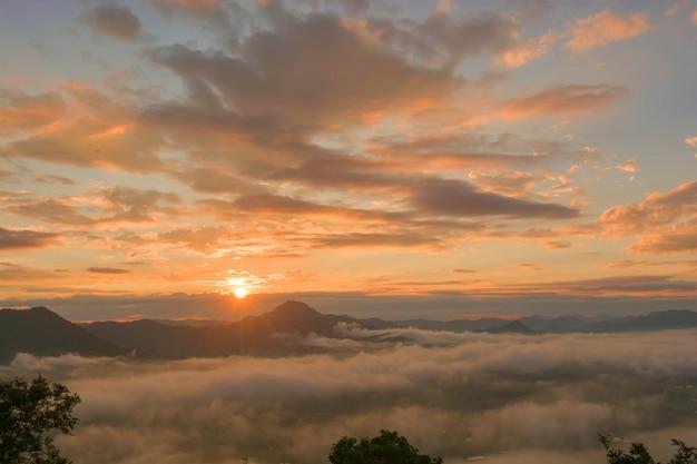 Salida del sol sobre la montaña con niebla en la mañana