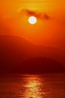 Salida del sol sobre la vista del océano atlántico desde la playa de copacabana, río de janeiro de brasil