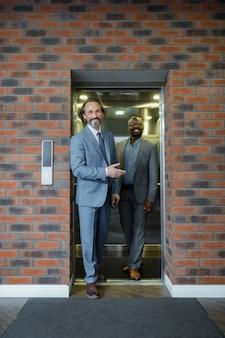 Saliendo del ascensor. dos hombres de negocios dejando el ascensor sonriendo antes de una importante negociación con los socios