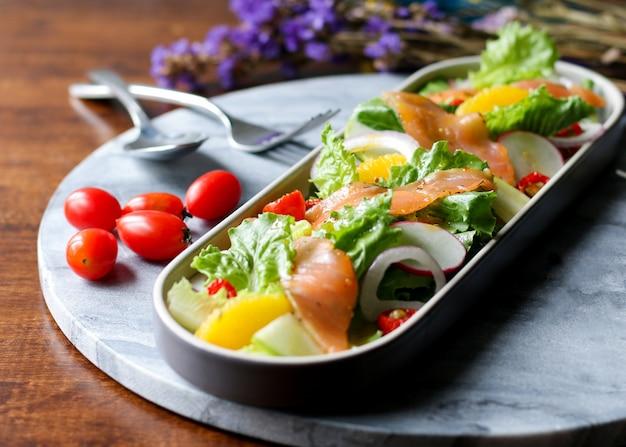 Salmón ahumado con lechuga mixta, aguacate, alcaparras y cebolla.
