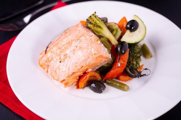 Salmón al horno con verduras en un plato blanco