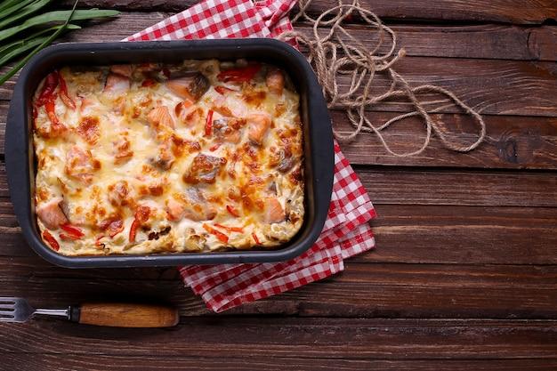 Salmón al horno con verduras y queso sobre un fondo de madera