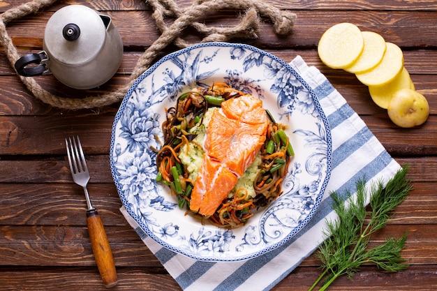 Salmón asado con verduras en la mesa