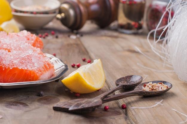 El salmón se corta y se espolvorea con sal y especias sobre una tabla de madera.