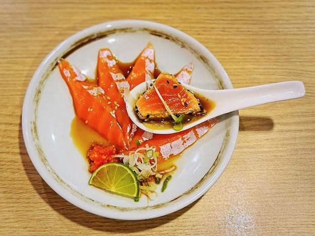 Salmón crudo en rodajas con salsa ponzu agria en un plato pequeño