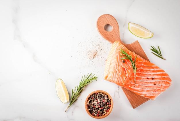 Salmón fresco de pescado crudo, filete de ternera, con especias, lima, romero, sal