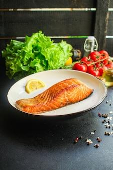 Salmón frito pescado parrilla barbacoa porción de mariscos comida en la mesa