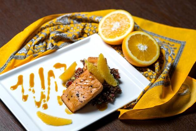 Salmón frito servido con arroz naranja y rojo.