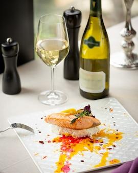 Salmón frito con verduras y una copa de vino blanco.