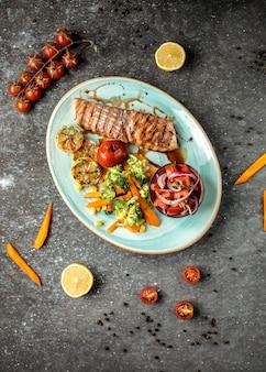 Salmón frito con verduras sobre la mesa