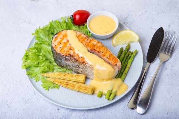 Salmón a la parrilla con espárragos, mini maíz y salsa holandesa. de cerca.