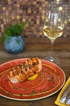Salmón a la parrilla servido con limón y vino blanco.