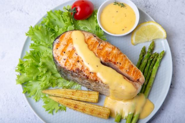Salmón a la plancha con espárragos, mini maíz y salsa holandesa. de cerca.