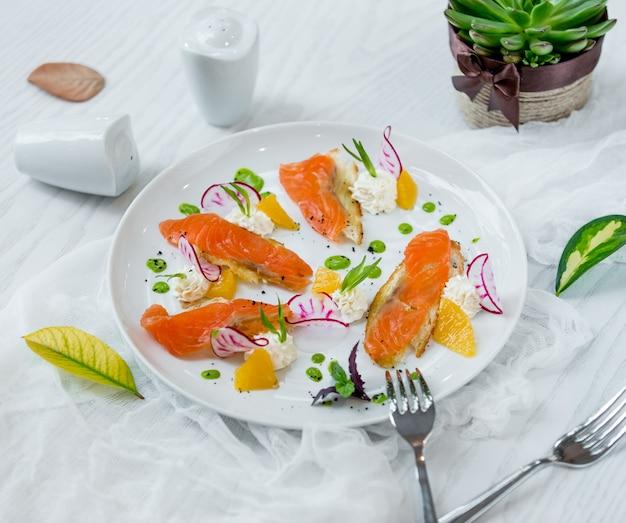 Salmón con rodajas de naranja en el plato