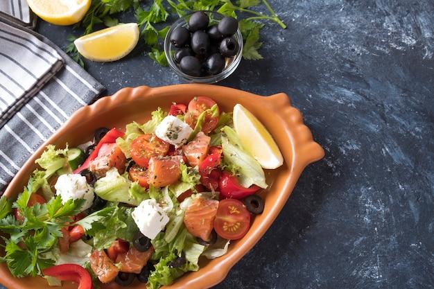 Salmón con verduras, queso y aceitunas negras en un plato. comida dietetica.
