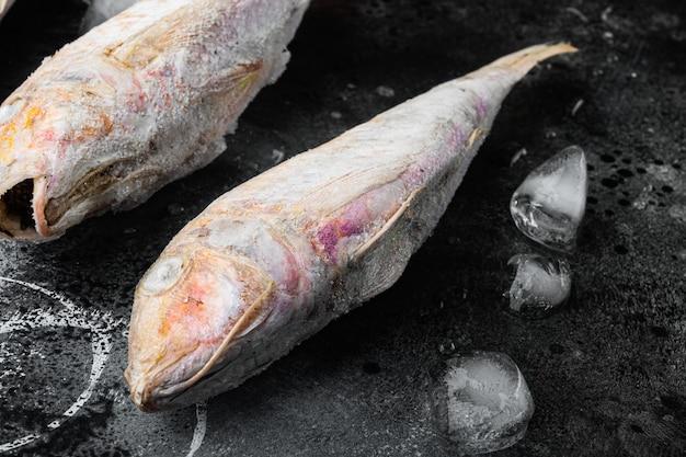 Salmonete congelado o pescado crudo barabulka, sobre fondo de tabla de piedra oscura negra