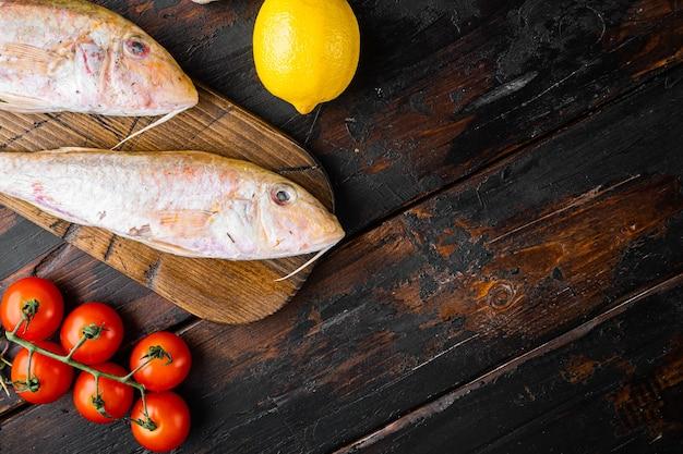 Salmonete crudo o sultanka conjunto de pescado entero fresco, con ingredientes y hierbas, sobre fondo de mesa de madera oscura vieja, vista superior plana, con espacio de copia para texto