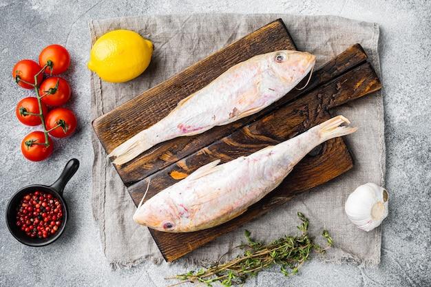 Salmonete crudo o sultanka conjunto de pescado entero fresco, con ingredientes y hierbas, sobre fondo de mesa de piedra gris, vista superior laicos plana
