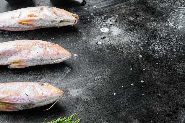 Salmonete crudo o sultanka conjunto de pescado entero fresco, con ingredientes y hierbas, sobre fondo de mesa de piedra oscura negra, con espacio para copiar texto