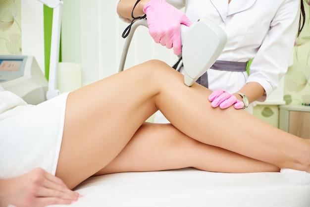 Salón de belleza, depilación láser, médico y paciente.