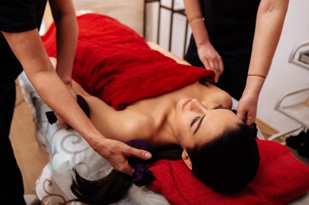 Salón de belleza profesional. mujer desnuda cubierta con una toalla roja descansando sobre una cama de masaje mientras los maestros acarician suavemente su cuerpo
