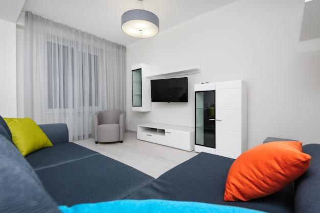 Salón blanco con televisor y sofá.