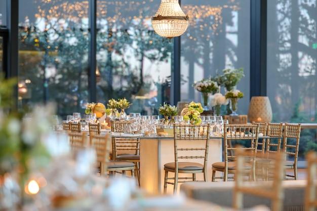 Salón de bodas decorado con una hermosa mesa con decoraciones florales