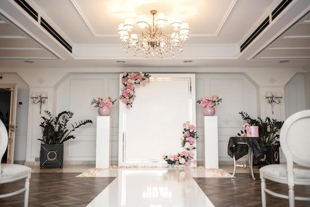 Salon de bodas. filas de sillas blancas festivas para invitados. arco de bodas para los novios.
